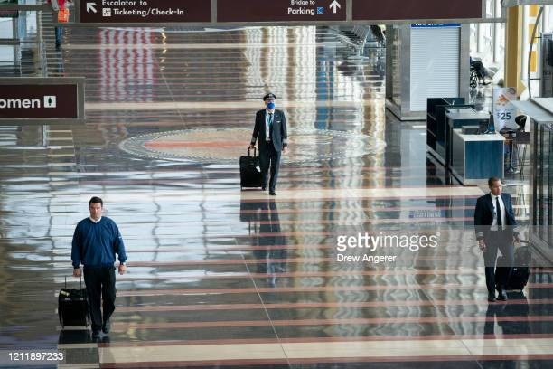 A pilot wears a face covering as he walks through a mostly empty terminal at Ronald Reagan Washington National Airport May 5 2020 in Arlington...