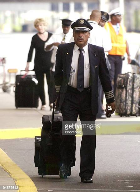 A pilot wheels his suitcase near the US Airways terminal at Philadelphia International Airport in Philadelphia Pennsylvania Thursday September 14...