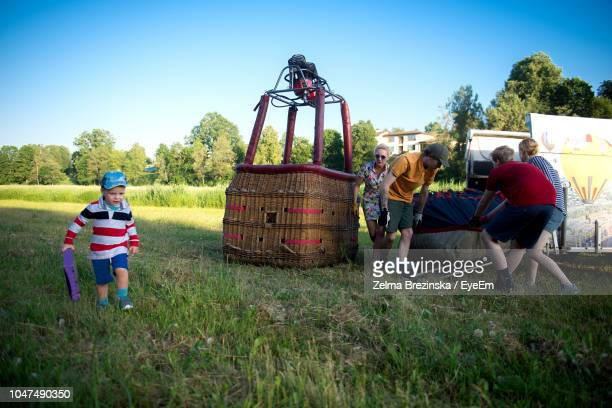 Pilot With Family Preparing Hot Air Balloon On Grassy Field Against Clear Sky During Sunset