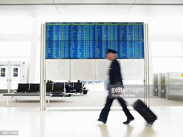Pilot with luggage walking past departure board