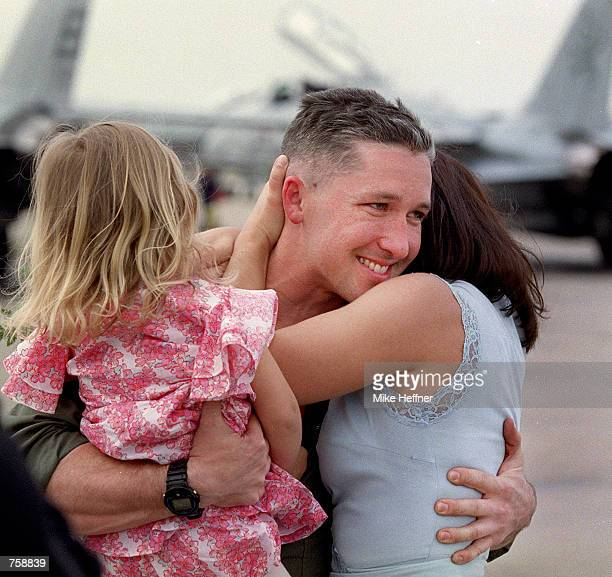 F14 pilot Zach Mosedale embraces his daughter Zoe and wife Cara at Naval Air Station Oceana March 26 2002 in Virginia Beach VA The F14 Tomcat...