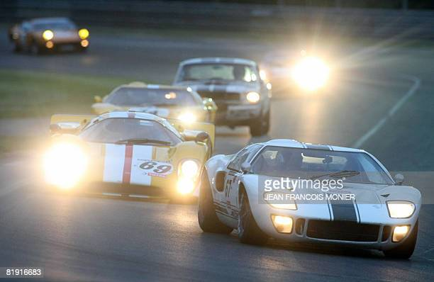 US pilote Tom Mabey drives a 1966 Ford GT 40 ahead of portuguese Carlos Barbot on a Lola MK III drives by portuguese pilote during the 'Le Mans...