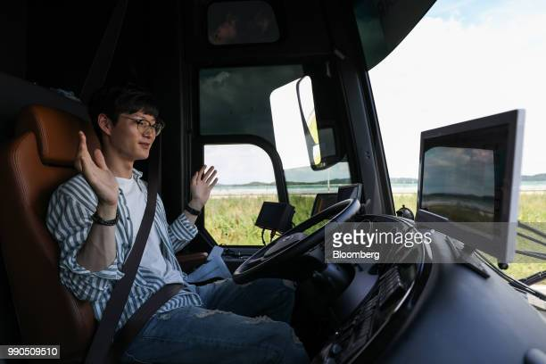 A pilotraises hands as he sits inside an autonomous 5G connected bus operated by KT Corp during a test drive at KCity in Hwaseong South Korea on...