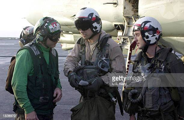 Pilots and aircrew brief a plane captain on the performance of an F14 Tomcat after completing a mission over Afghanistan October 17 2001 aboard the...