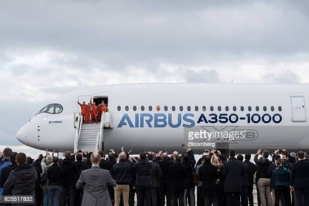Pilots and crew members wave from the door of a Airbus A3501000 twinjet passenger plane manufactured by Airbus Group SE after landing following its...