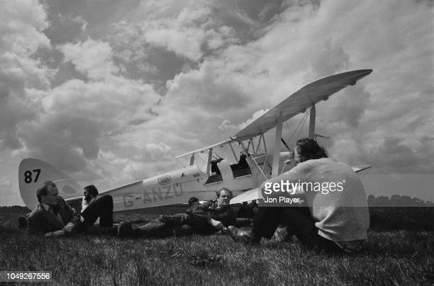 Pilots and visitors resting near a de Havilland Tiger Moth aircraft during the Biggin Hill Air Fair, UK, 27th July 1979.