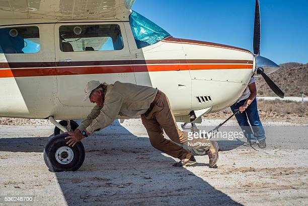 Pilots Andre and Kyle Schoeman push their airplane closer to a runway at the Flyin competitions on Saturday May 28 in Uis Namibia Sixteen aircraft...
