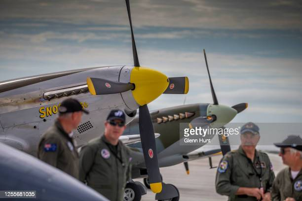Pilots are seen standing underneath wartime airplanes the P51D Mustang and Mark 16 Spitfire on Brisbane's new Runway at an event to celebrate the...
