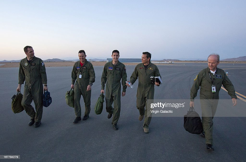 Pilots, (L-R) Clint Nichols,Mike Alsbury,Brian Maisler, Mark Stuckey and Dave McKay of Virgin Galactic's WhiteKnight2 and SpaceShip2 walk towards the aircraft for the first rocket powered flight (PF01) since the beginning of the program that began in 2005 on April 29, 2013 in Mojave, California. SpaceShipTwo is a private enterprise aircraft, designed to carry paying passengers into space. The spacecraft was dropped from the mothership at high altitude and fired it's engine for a approximate 16-second burn taking the craft through the sound barrier. The hybrid rocket motor is fueled by nitrous oxide and a rubber propellent combination. The motor can be 'shut down' at any time for safety and flight requirement purposes.