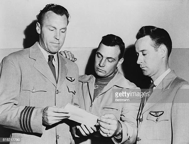 Pilots EJ Smith Kenneth Arnold and Ralph E Stevens look at a photo of an unidentified flying object which they sighted while en route to Seattle...