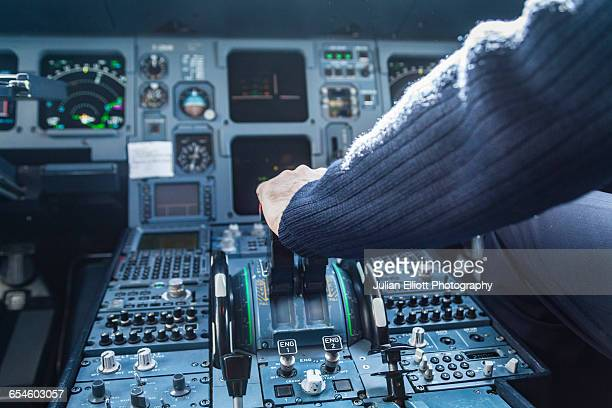A pilot's hand on the throttle of a plane.
