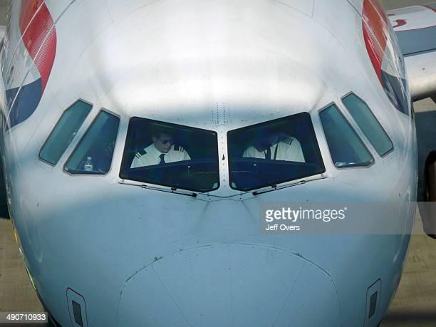Pilots in a BA British Airways passenger aircraft plane at Heathrow Airport terminal Five landscape format