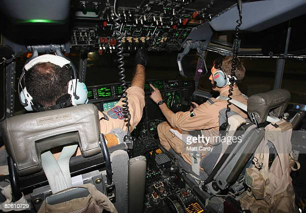 Pilots in a RAF Hercules at Al Udeid Air Base prepare the aircraft for takeoff to take passengers including rugby players Scott Gibbs and Ieuan Evans...