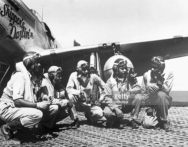 Pilots of a P51 Mustang Group of the 15th Air Force in Italy kneel before the Mustang aircraft Skipper's Darlin' III August 1944