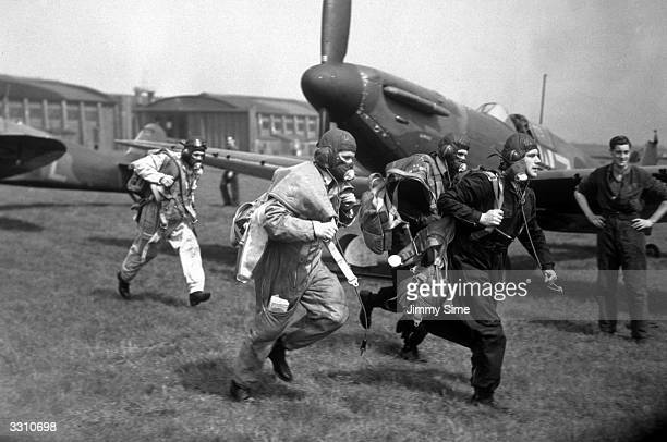 Pilots of No 19 Squadron Royal Air Force Fighter Command scramble to their wooden twoblade fixedpitch propellered Supermarine Spitfire MkI fighter...