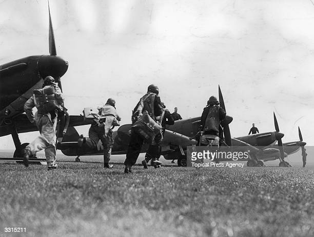 British pilots in full kit running towards their waiting planes after receiving a general warning from coastal observation stations