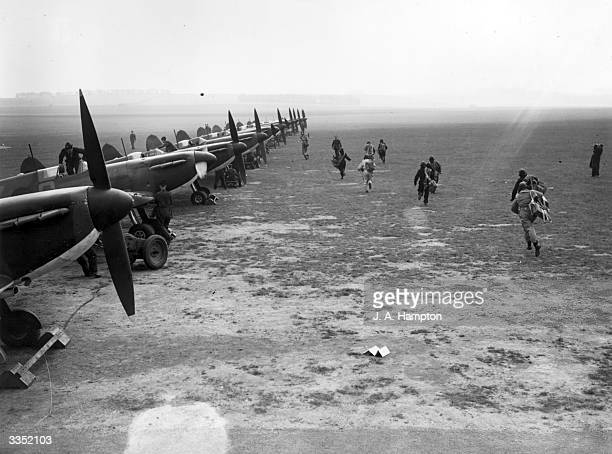 Pilots of No 19 Squadron, Royal Air Force Fighter Command scramble to their wooden, two-blade, fixed-pitch propellered Supermarine Spitfire MkI...