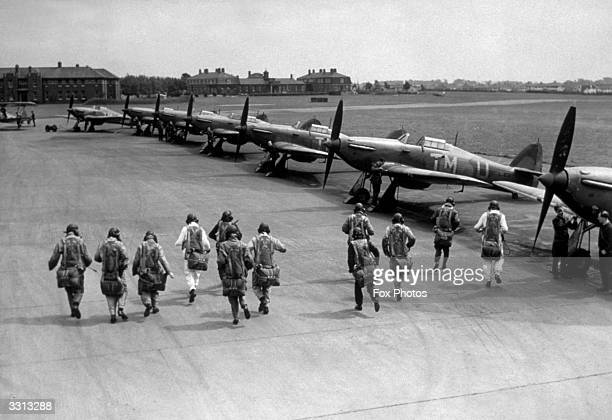 Pilots of No111 Squadron Royal Air Force Fighter Command make a practice scramble to board their Hawker Hurricane Mk1 monoplane fighters with their...