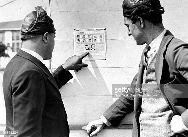 Pilots Paul Herman and Bill Ward look at poster of John Dillinger