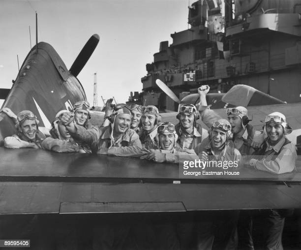Pilots pleased over their victory during the Marshall Islands attack grin across the tail of an F6F Hellcat on board the USS Lexington after shooting...