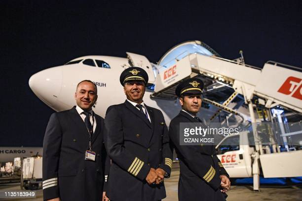 Pilots pose for a photo in front of a cargo plane on the tarmac of the Ataturk Airport on the last day of flight operations of the Ataturk...
