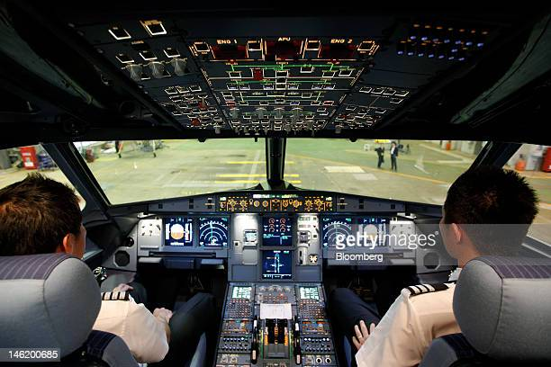 Pilots sit in the cockpit of Jetstar Japan Co's Airbus SAS A320 aircraft during a media preview at Narita Airport in Narita City Chiba Prefecture...