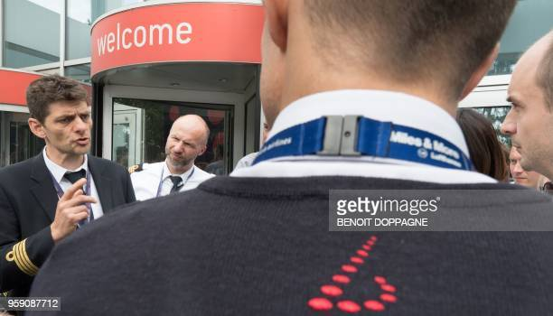 Pilots speak as they wait outside while negotiations start between pilots and management at Brussels Airlines headquarters in Diegem on May 16 during...