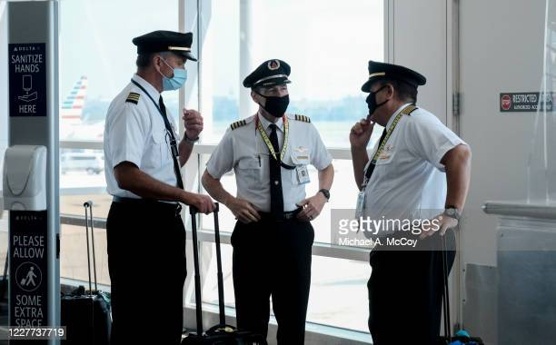Pilots talk after exiting a Delta Airlines flight at the Ronald Reagan National Airport on July 22, 2020 in Arlington, Virginia. During the COVID-19...