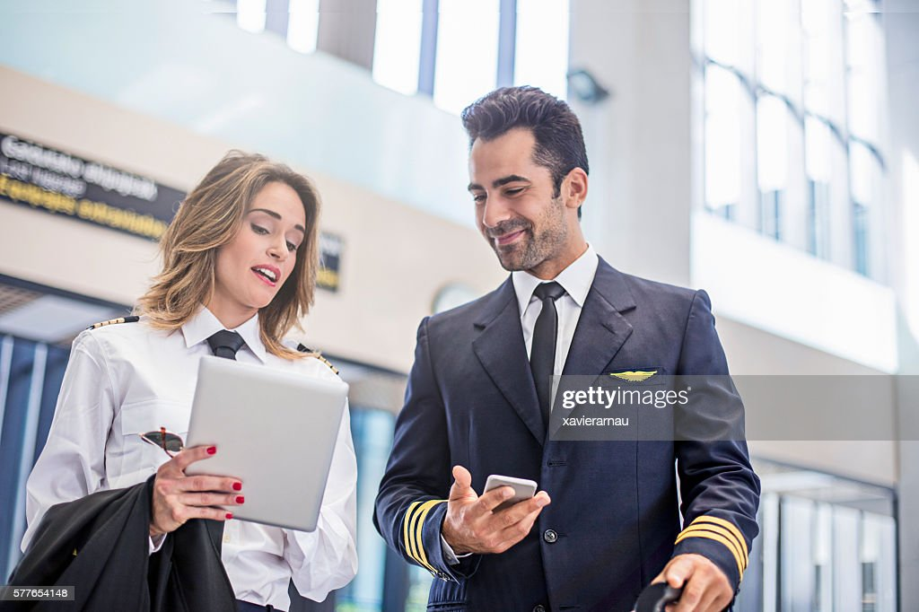 Pilots using digital tablet on the way to the plane : Stock Photo