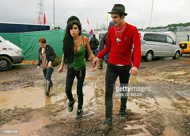 British pop singer Amy Winehouse walks through the mud to the Pyramid stage with an unidentified friend as she prepares to perform at the Glastonbury...