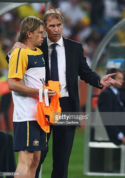 Pim Verbeek head coach of Australia speaks with Brett Holman of Australia as he brings him on as a substitute during the 2010 FIFA World Cup South...