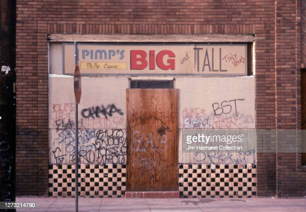 Pimp's Big and Tall on 1st Street in Los Angeles, California has a deteriorating facade covered in graffiti, 1991.