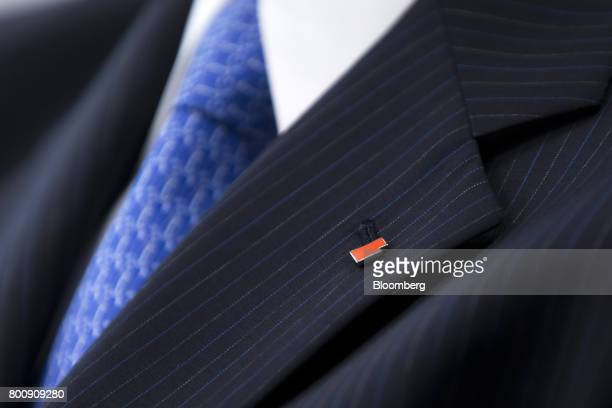 A pin in the shape of the Takata Corp logo is displayed on an employee's lapel during a news conference in Tokyo Japan on Monday June 26 2017 Takata...