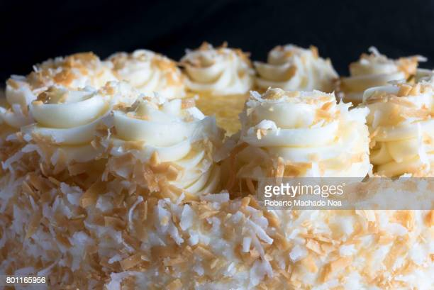 Pina Colada Cake Small round butterscotch icing cake with shredded coconut and white swirl drops around edges against a dark background