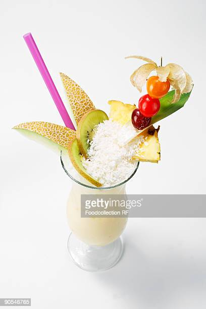 Pina colada garnished with fruit and grated coconut, close Up