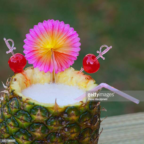 Pina colada in a pineapple with cherries as garnis