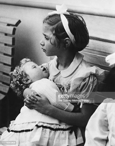Pina Laconesi holds her sleeping sister Rina as their parents cope with customs on arrival in Sydney on board the Neptunia 22 November 1955