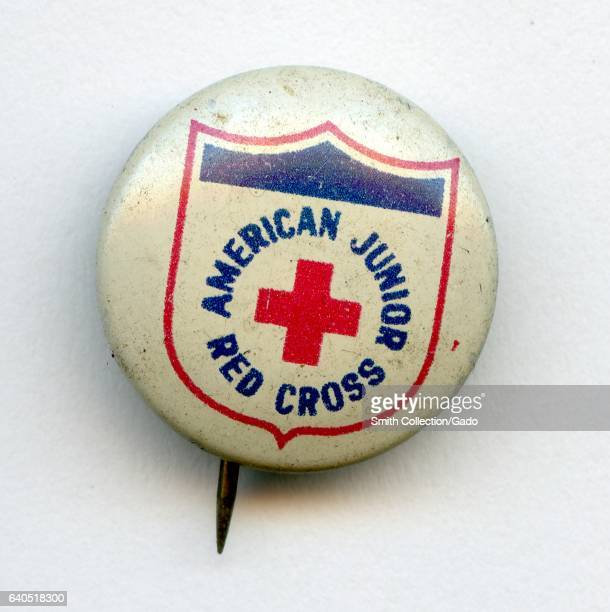 Pinback button with red white and blue coloring and lettering reading American Junior Red Cross 1940