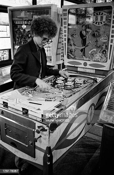 Pinball player in France Young boy playing pinball
