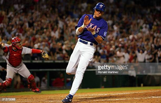 Pinch runner Andy Fox of the Texas Rangers claps as he scores on an RBI from Laynce Nix in the eighth inning against the Anaheim Angels on September...