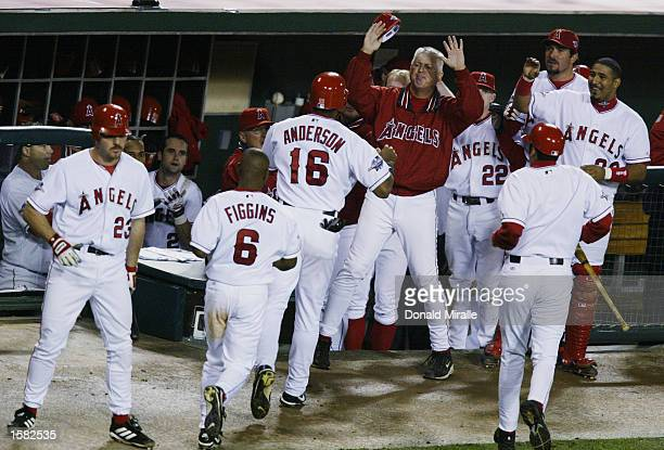 Pinch runner Chone Figgins and Garret Anderson of the Anaheim Angels celebrates scoring with his team on a double by teammate Troy Glaus in the...