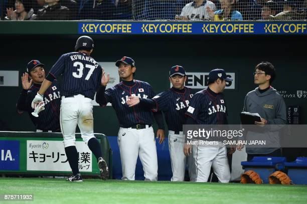 Pinch runner Outfielder Masayuki Kuwahara of Japan high fives with team mates after scoring a run by the RBI single of Infielder Yota Kyoda in the...