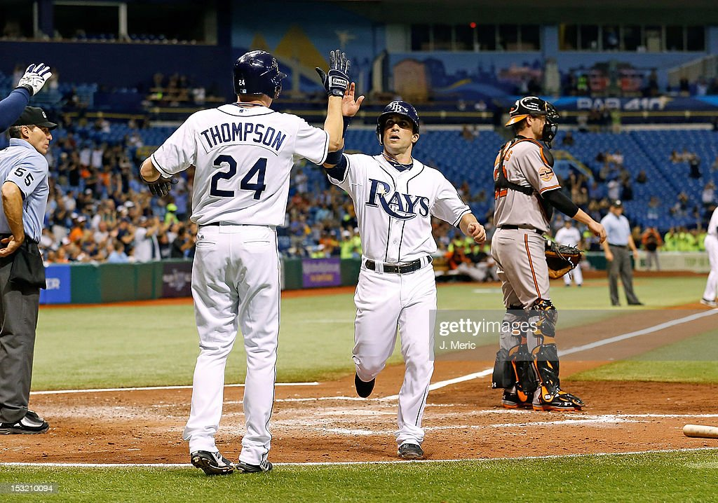 Pinch runner Rich Thompson #24 of the Tampa Bay Rays congratulates Sam Fuld #5 after they both scored against the Baltimore Orioles during the game at Tropicana Field on October 1, 2012 in St. Petersburg, Florida.
