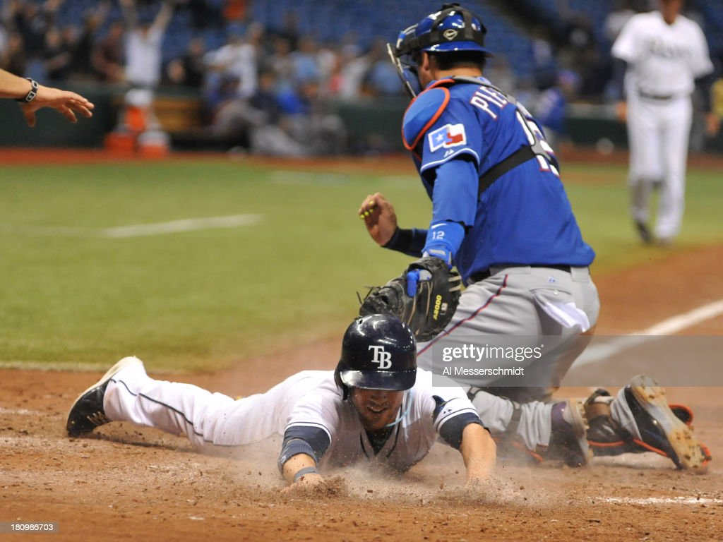 Pinch runner Sam Fuld #5 of the Tampa Bay Rays dives for home plate and scores the winning run in the 12th inning against the Texas Rangers September 18, 2013 at Tropicana Field in St. Petersburg, Florida. The Rays won 4 - 3.