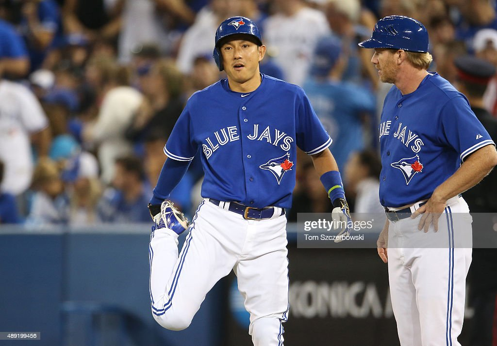 Pinch-runner Munenori Kawasaki #66 of the Toronto Blue Jays stretches as he comes into the game in the eighth inning as first base coach Tim Leiper #34 looks on during MLB game action against the Boston Red Sox on September 19, 2015 at Rogers Centre in Toronto, Ontario, Canada.