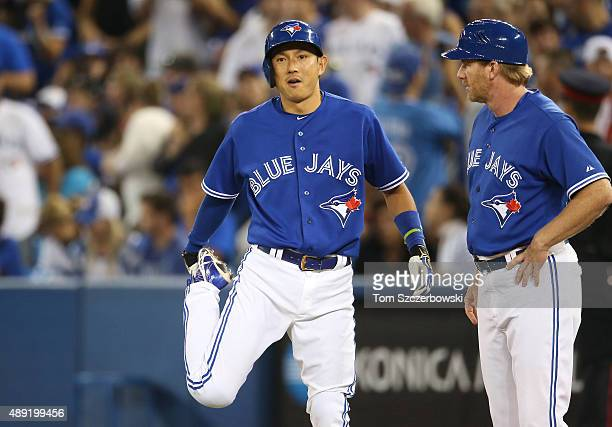 Pinchrunner Munenori Kawasaki of the Toronto Blue Jays stretches as he comes into the game in the eighth inning as first base coach Tim Leiper looks...