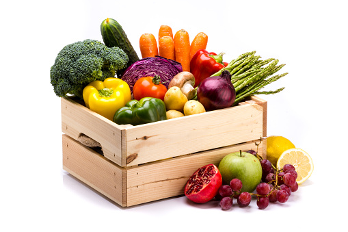 Pine box full of colorful fresh vegetables and fruits on a white background 1051343392