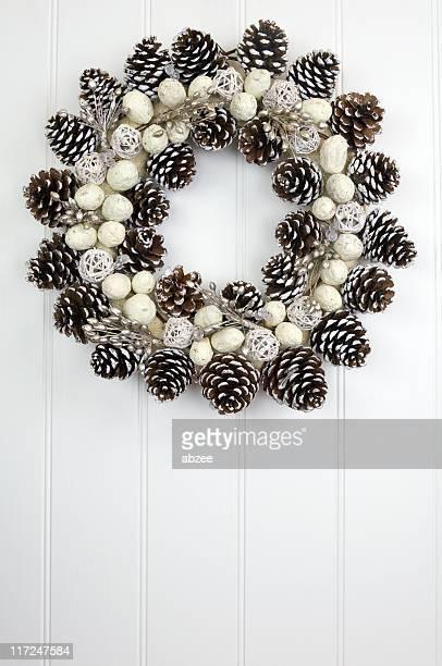 Pine cone wreath on white paneled wall