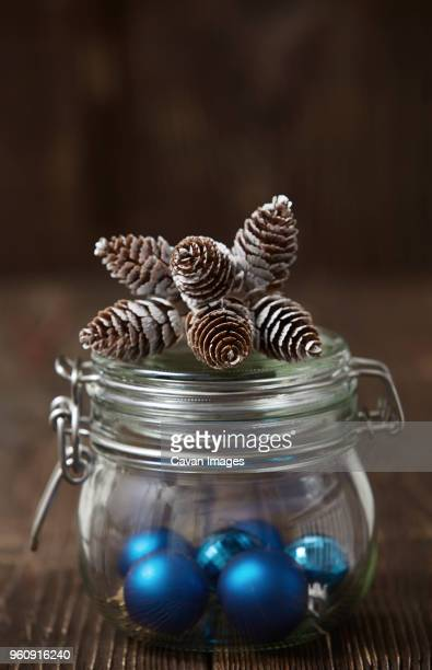 Pine cones on container with Christmas ornaments