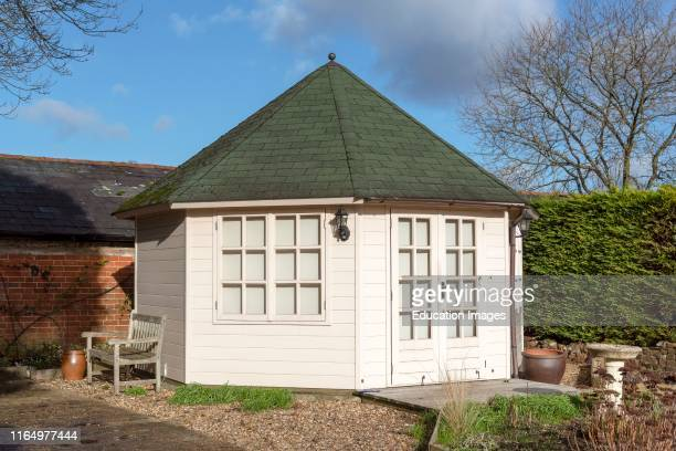 Pine constructed garden office with decking area and landscaped garden viewed in winter Situated in Southern England UK
